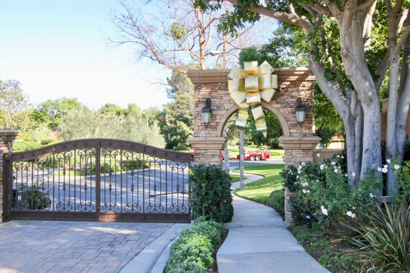 A large, golden bow sits over an archway at the Turtle Rock Pointe community.