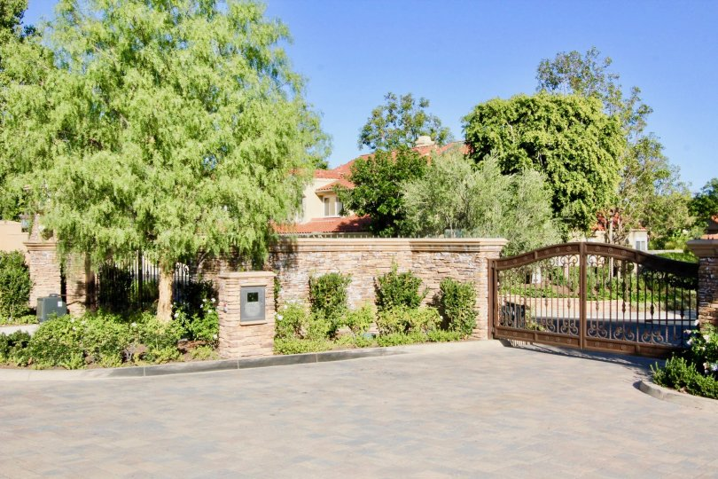 gate driveway tree garden western west coast sun outdoors upperclass fancy stone fence metal