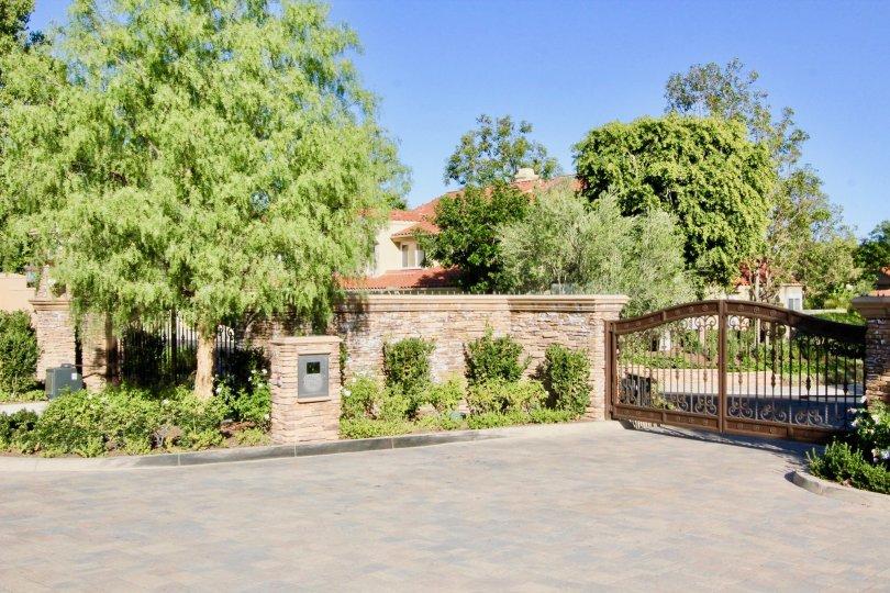 gate driveway tree garden western west coast sun outdoors upperclass fancy stone fence metal