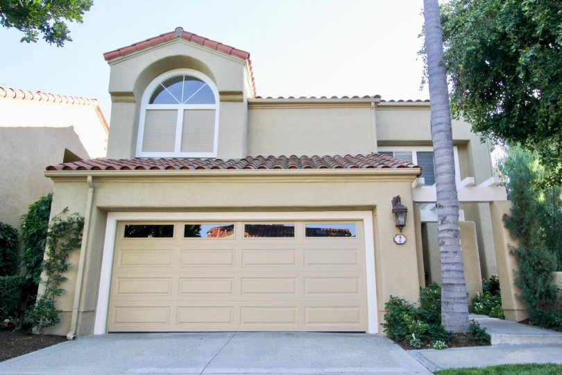 a tan home in Turtle Rock Pointe with a palm tree and a large window