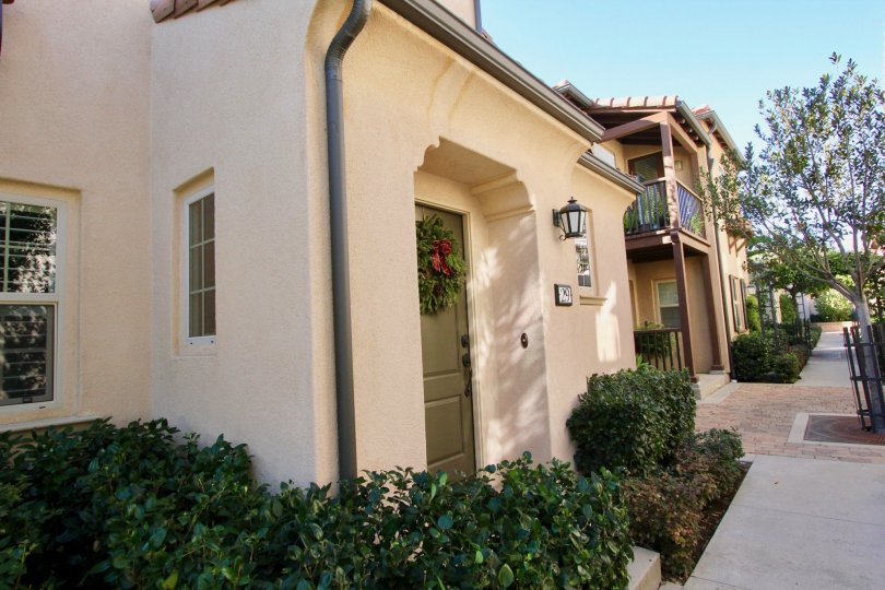 An entry to a home in Vientos showing the unit placard and landscaping