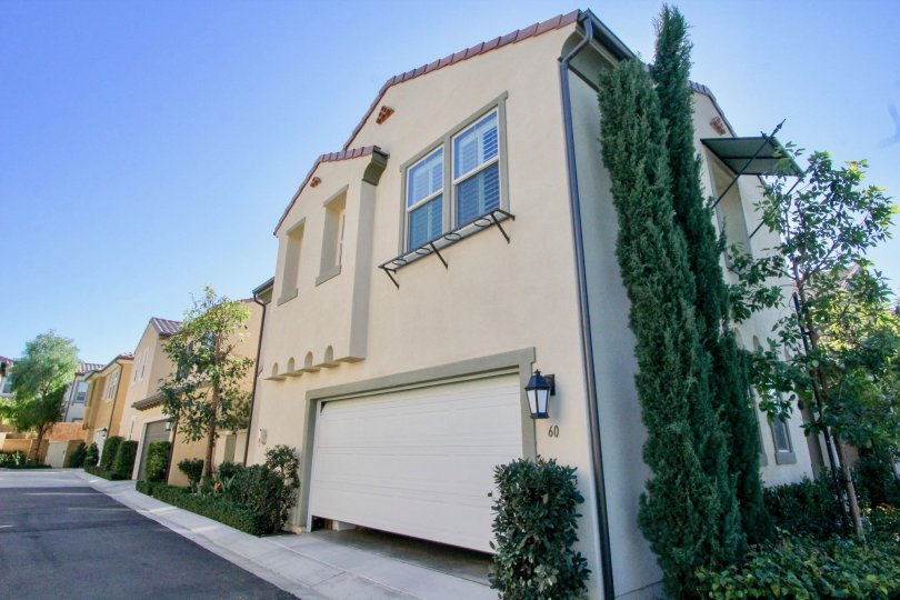 Two story home with a partially open garage inside Vientos in Irvine CA