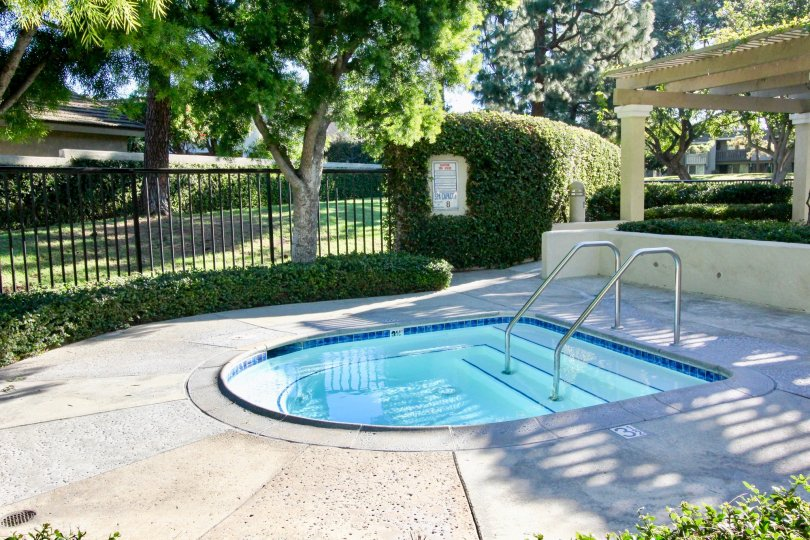 Shield shaped hot-tub behind a black iron fence inside Village Glen in Irvine CA
