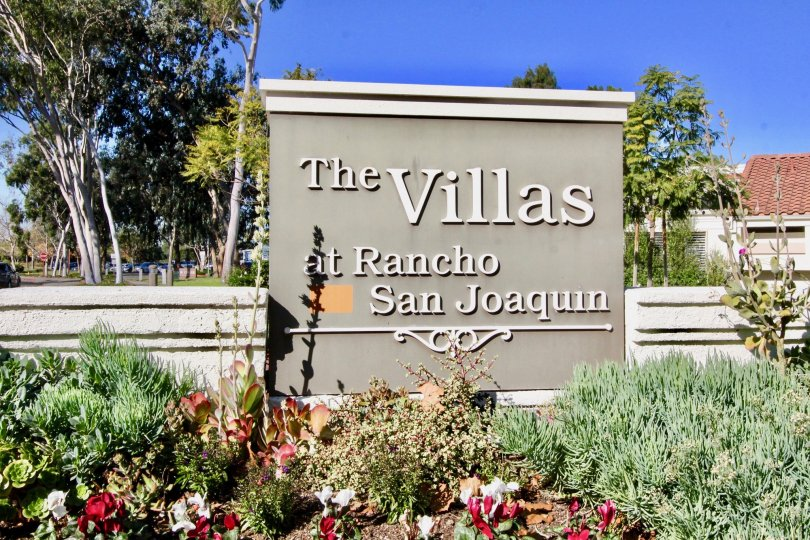 A large gray and white sign behind a garden at Villas at RSL in Irvine CA
