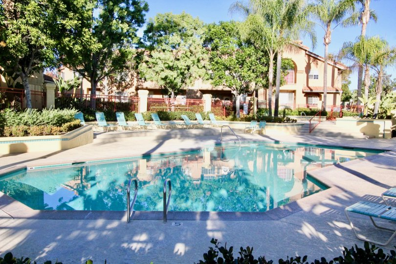 A clear blue swimming pool outside of a large house in Irvine California.