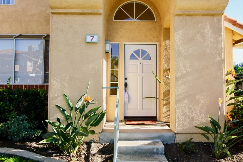 A bright yellow stucco house with a white door and the house number 7 painted on the front porch in Irvine, CA.