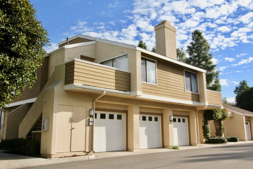 A tan building with three garages in Windwood townhomes community in Irvine, California.