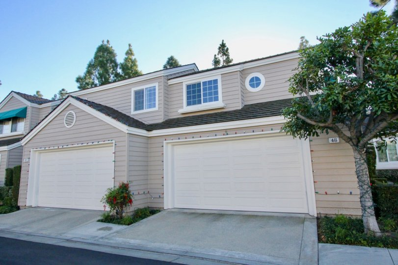 Two large white garage doors attached to gray homes at Woodbridge Cove in Irvine CA