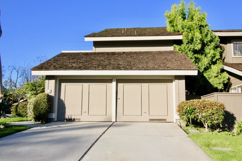 Sunny day looking at two garage doors on a home found in the Woodbridge Crossing community of Irvine, California