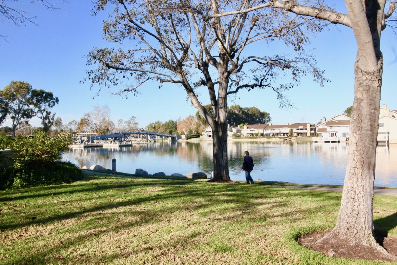 A person walking along the water with boats in the Woodbridge Grove community in Irvine, California.