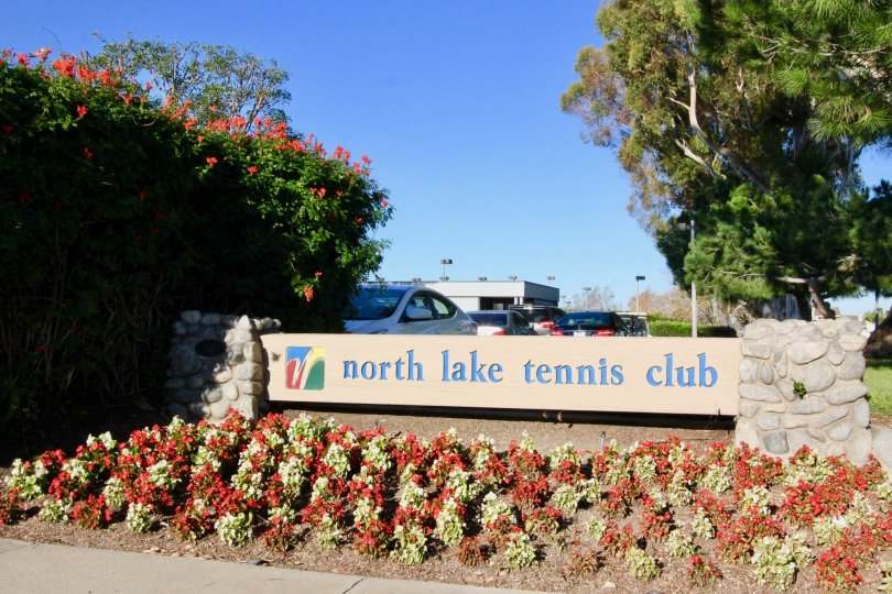 A tennis club signpost in the Woodbridge Grove community surrounded by reddish blooms.