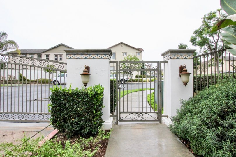 A estate in brio with beautiful front gate. surrounding is full of garden with plants and trees.
