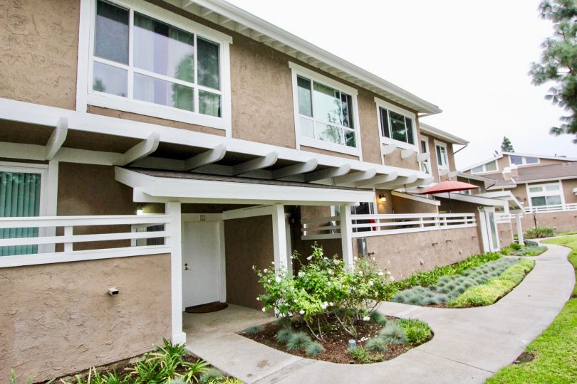 A sunny day in coyote creek with bewitching row homes and lawns, trees and plants