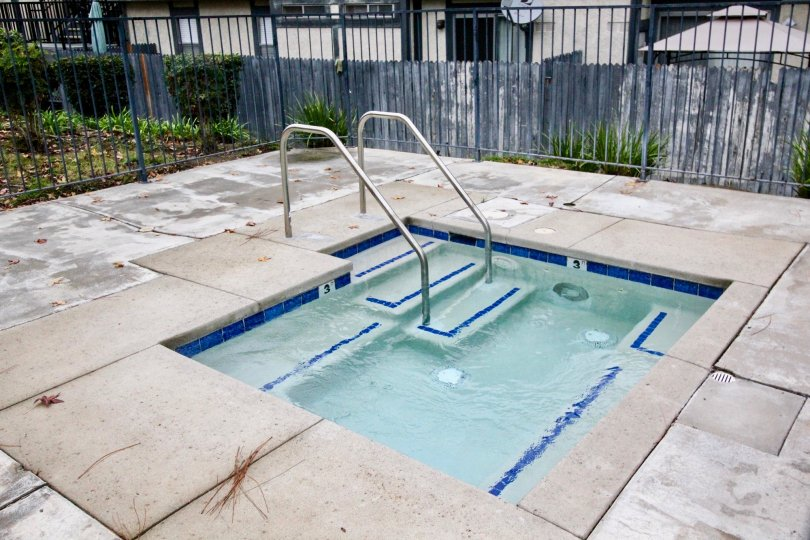 A small swimming pool in the Heritage Walnut covers with some iron grill and some shrubs.