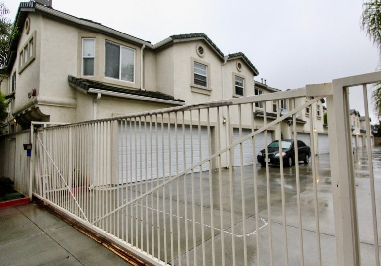 The row home in la habra glen with long gate entrance and cars