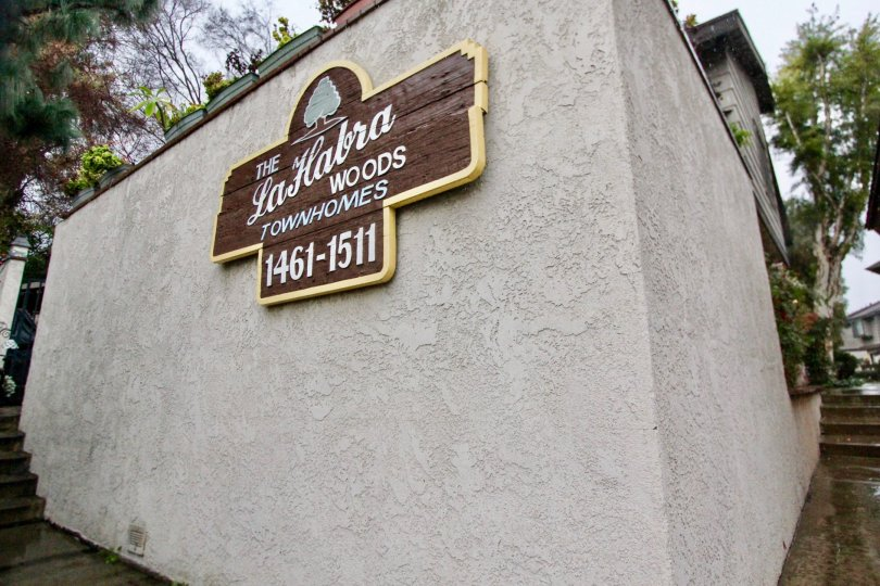 THE ENTRANCE WAY NAME BOARD ON THE WALL BESIDE MANY PLANTS TREES ARE THERE IN LA HABRA CITY