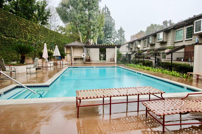 A PLEASANT DAY IN THE La Habra Woods Townhomes WITH A BUILDING THAT HASswimmingpool AND RESTING TABLES