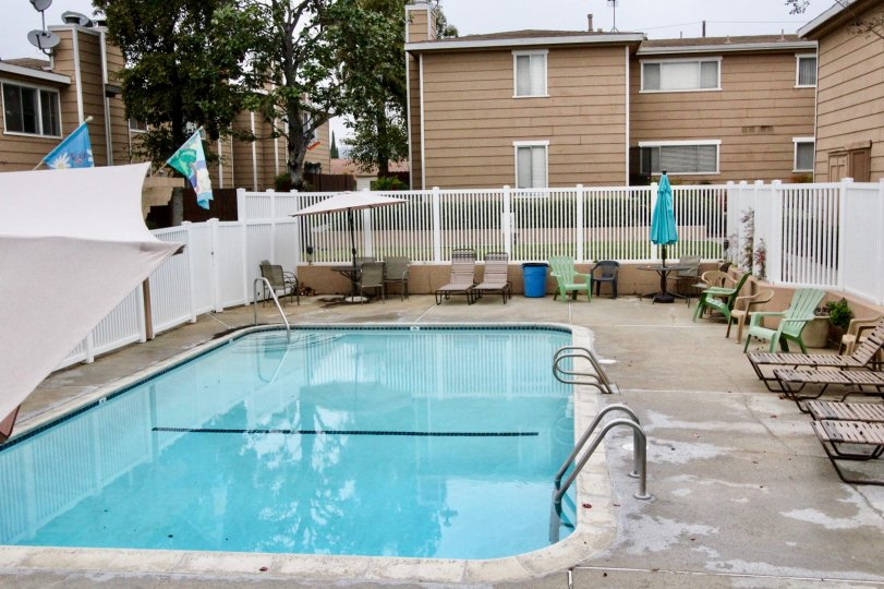 THIS IMAGE SHOWS THE SWIMMING POOL WITH LOT OF CHAIRS BACKSIDE VILLAS, LEFT SIDE FLAGS, UMBRELLA ARE VISIBLE IN IMAGE IN LA HABRA CITY