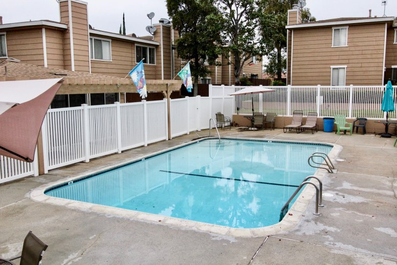 An outdoor pool in the La Plaza Habra area of La Habra, California with umbrellas, lawn chairs, and surrounding townhouse complexes
