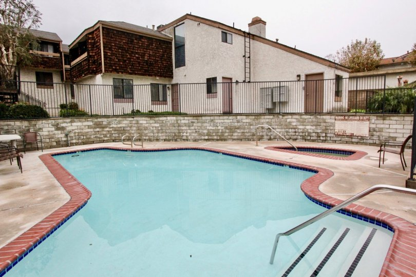 THIS IMAGE SHOWS THE SWIMMING POOL IN LA HABRA, THAT SHOWS THE CHAIRS, PLANTS NEARBY HOMES