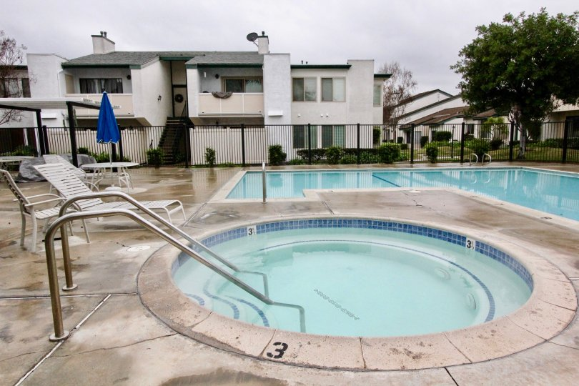 Awesome swimming pools with sitting place and trees beside villas in Smoketree of La Habra