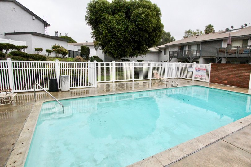 THIS IMAGE SHOWS THE SWIMMING POOL IN LA HABRA THAT HAVE THE CHAIRS, ON THE LEFT SIDE PLANTS AND TREES ARE THERE
