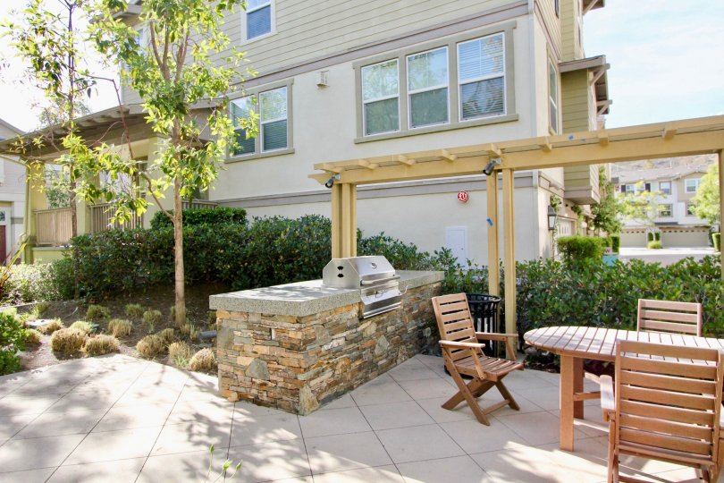 A view of the back of a townhome in Briar Rose Community in Ladera Ranch, California. This view is of the patio, grill and outdoor tables and chairs.