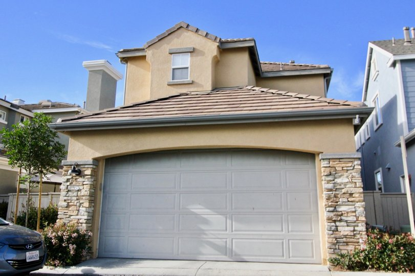 A tan home with stone around the garage door in St. Mays Road community in Ladera Ranch, California.