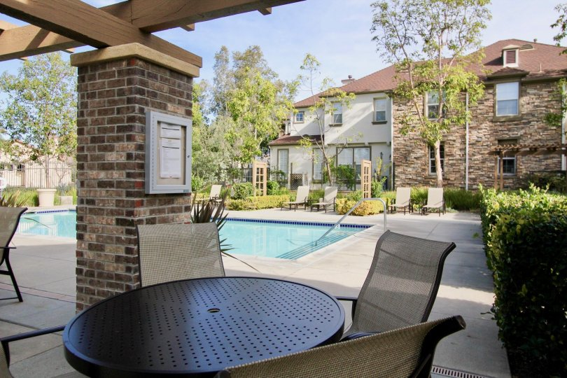 A sunny day in the area of Sycamore Grove, poolside, chair, patio, condo, bushes, stairs