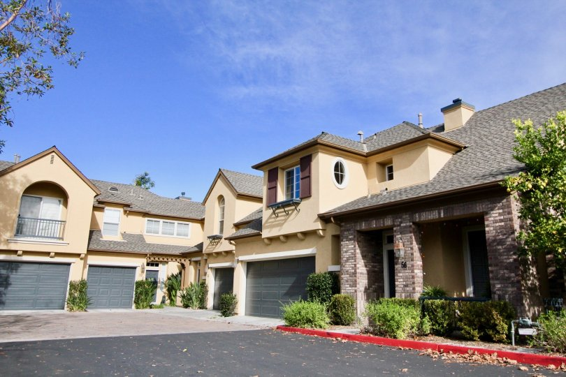 Homes with garages and stone pillars in Sycamore Grove community in Ladera Ranch, California.