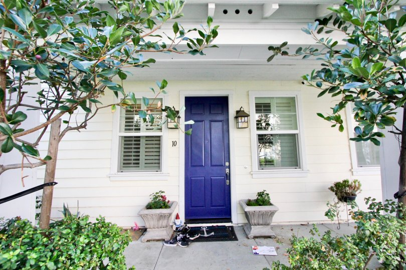 A dark blue door sits on a white house in Tarleton homes