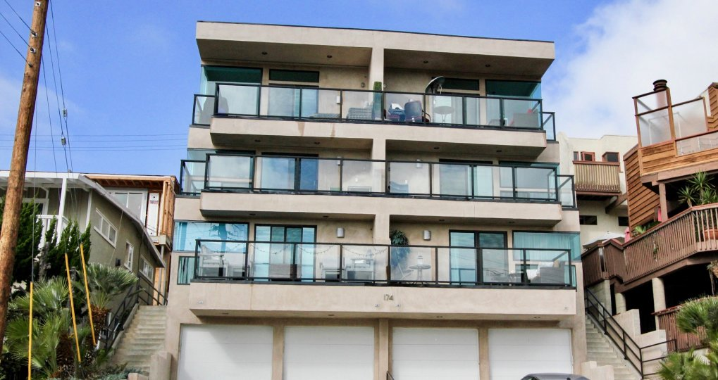 A bright day in the 174 Cliff Drive with a building and glass balcony.