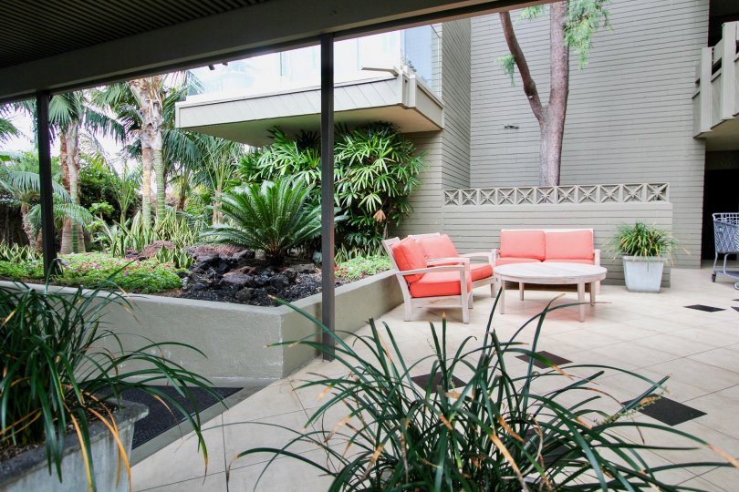 Outdoor patio with tile flooring, tropical foliage, and orange patio furniture in Laguna Lido