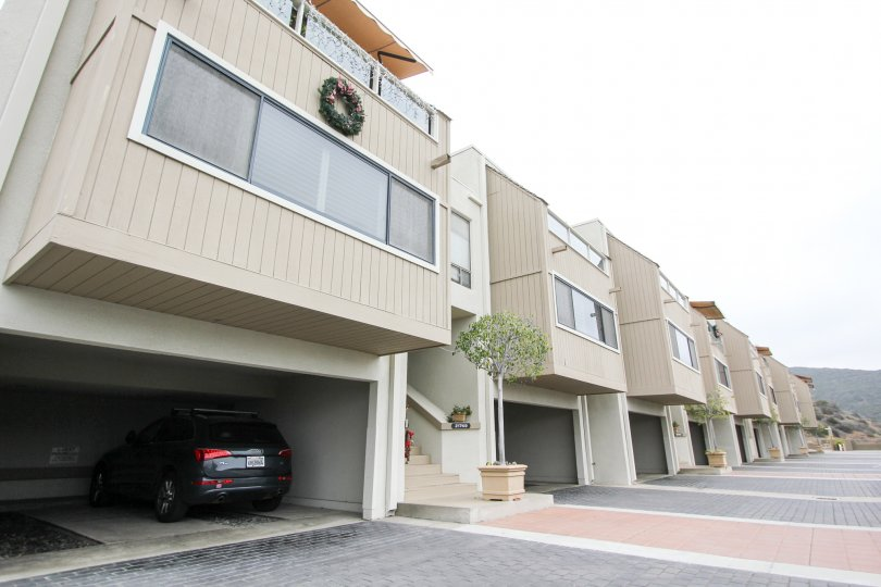 A day in the Laguna Ocean Vista with modern apartments and a vehicle.