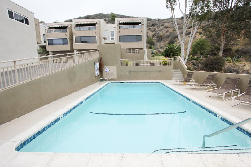 Buildings with view of a pool and hills in the Laguna Ocean Vista Community in Laguna Beach, CA.