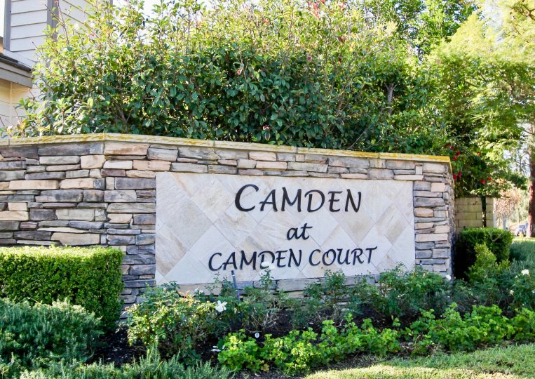 A stone wall with a sign informs visitors they have arrived at Camden at Camden Court