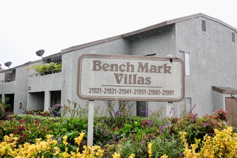 A gray building in the Bench Mark Villas community in Lake Forest, CA with yellow and purple flowers