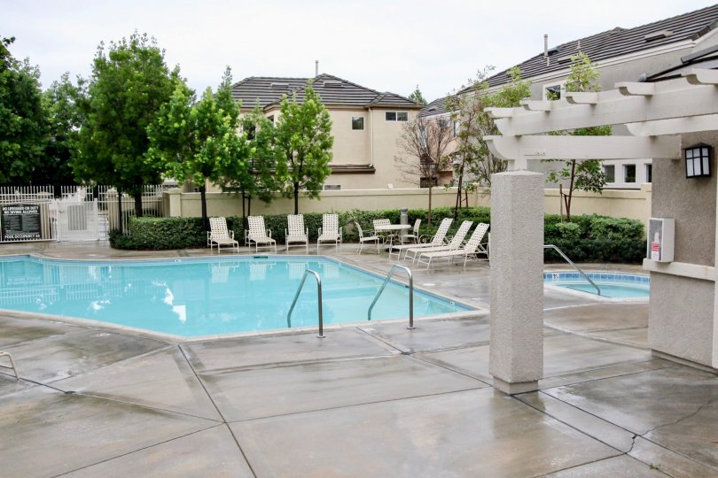 There are some white chairs nearby the swimming pool in the Brittany at Foothill Ranch.