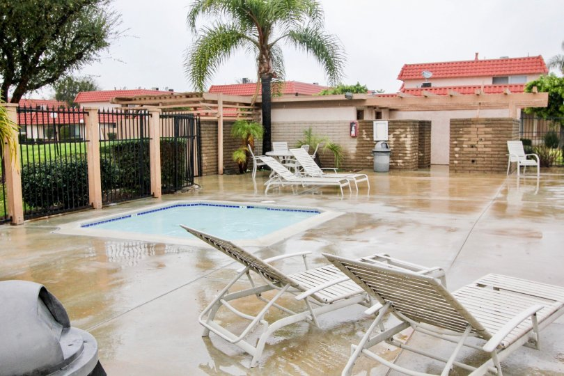 A small swimming pool in the Rancho Viejo Condos I with some chairs.