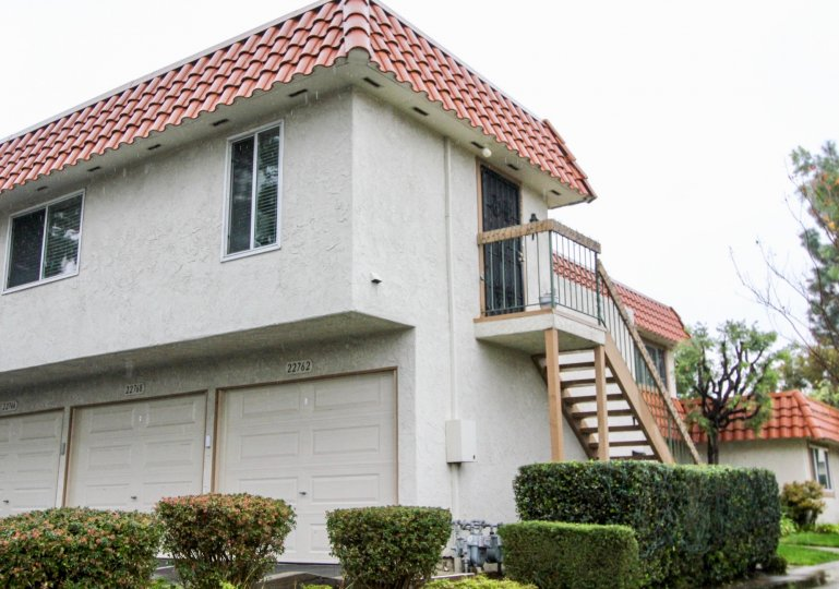 A white condos with red roof and stair case in Rancho Viejo Condos II community in Lake Forest, California.