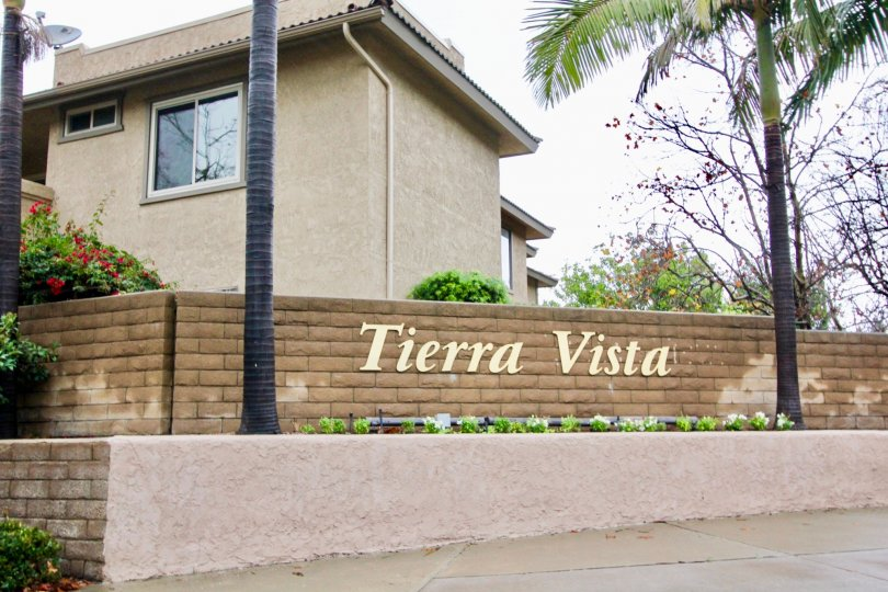 A sign is on the wall nearby a palm tree in the Tierra Vista.