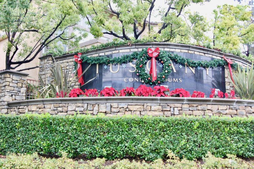 The entrance sign to Tuscany Condominiums at Foothill Ranch, decorated with a Christmas wreath and poinsettias.