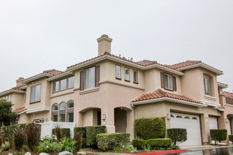 A very large tan home with bushes around it in California Terrace community in Mission Viejo, California.