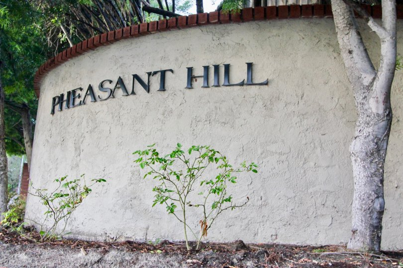 a pleasant day in the pheasant hill with a wall that has a treein front and named its community in it