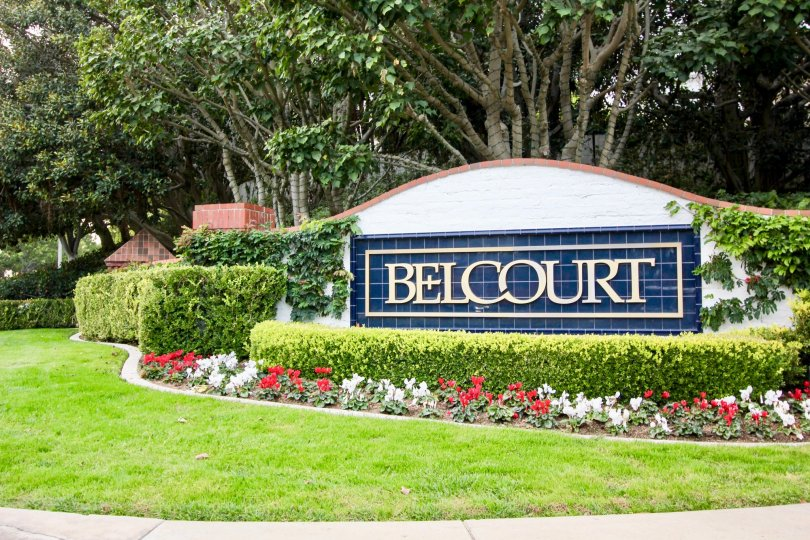 A beautiful garden surrounding the welcoming sign for the Belcourt Towne Collection in Newport Beach, CA