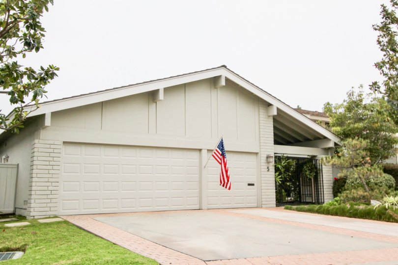 An American flag hangs from the wall of two garages of a white house in the Big Canyon Deane community in Newport Beach, California.