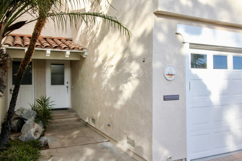 a warm day in the newport beach with house that has front of tree in stone, slide door