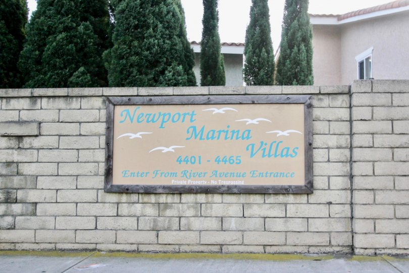 THE HOUSE IN THE NEWPORT MARINA VILLAS WITH THE NAME BOARD, TREES