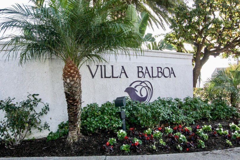 The Wall with Plants and bushes in Villa Balboa mentioned with community name with logo