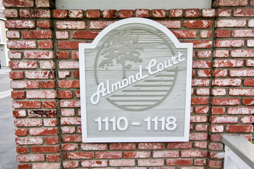 The gray sign for the Almond Court community with red brick